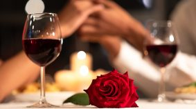 Romantic Date. Red Rose Lying On Table, Loving Afro Couple Holdi